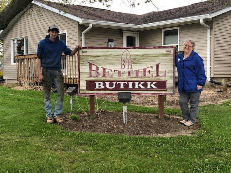 Two people standing next to the Bethel Butikk Food Pantry sign
