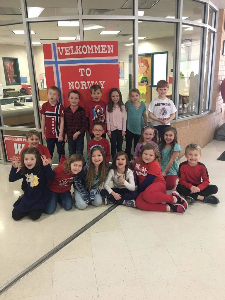 "Mrs. Vatland's class posing in front of a sign that says ""Velkommen to Norway."""