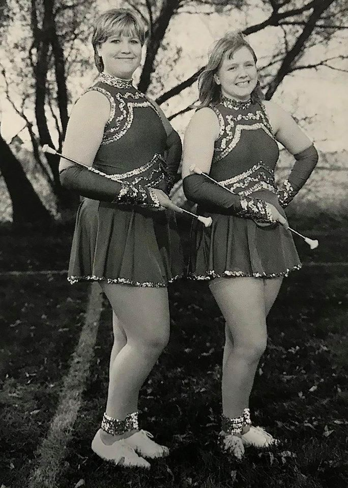 Two female student twirlers posing in costume with their batons